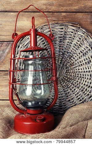 Kerosene lamp with wicker mat and burlap cloth on wooden planks background