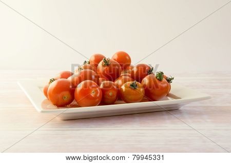 Bunch of red mini tomatoes on a square plate