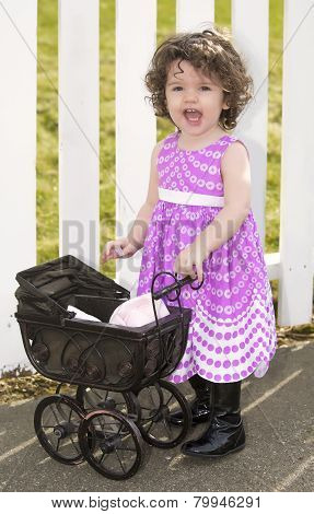 Little Girl In Pink Dress With A Pram