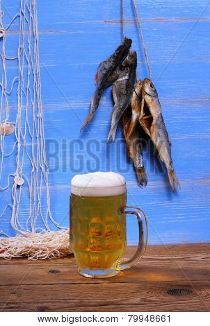 Mug Of Beer On Blue Background With Dried Rudd Fish