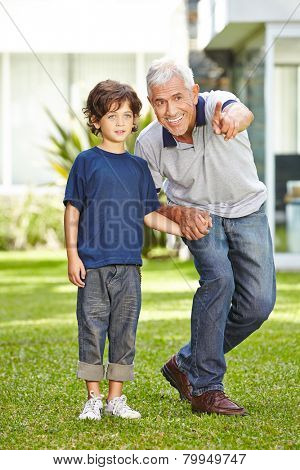 Happy grandfather playing with his grandson in a garden