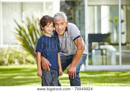 Happy grandfather talking with his grandchild in a summer garden