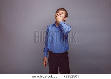 teenager boy yawns European appearance covers her mouth, drowsin