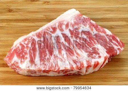 A piece of fresh and raw Beef hump on a wooden background