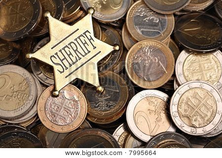 Heap of one and two euro coins with a sheriff star as bribery concept