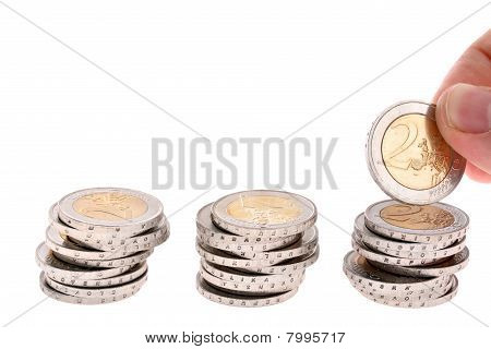 Hand puts a two-euro coin on third coin column isolated on white background
