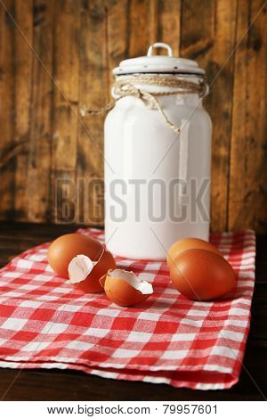 Milk can with eggs and eggshell on napkin on rustic wooden background