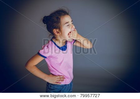 baby girl yawns closes her mouth on gray background