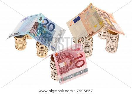 Three houses made of euro coins and paper money isolated on white background