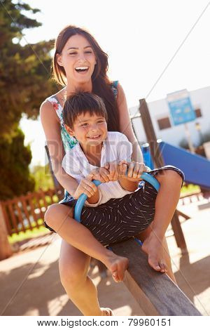 Mother And Son Having Fun On Seesaw In Playground