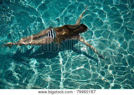 Woman Swimming On A Blue Water Pool