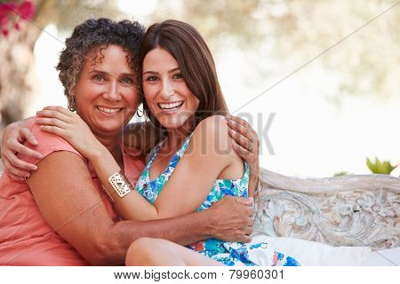 Portrait Of Mother With Adult Daughter On Garden Seat