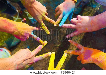 Friends Putting Their Hands Together In A Sign Of Unity And Teamwork. Holi Colors Festival