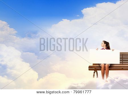Young woman with white blank banner sitting on bench