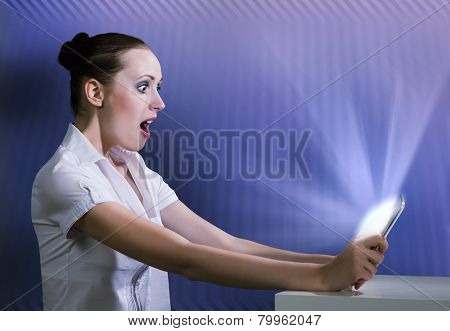 Young pretty surprised woman using tablet pc
