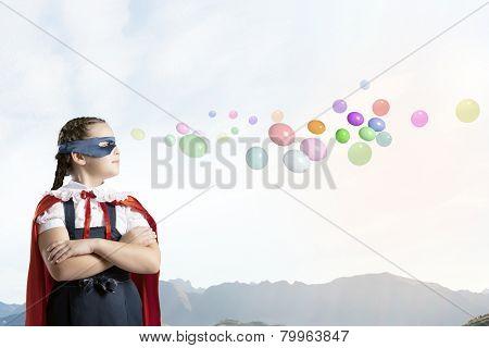 Cute girl of school age wearing super hero costume
