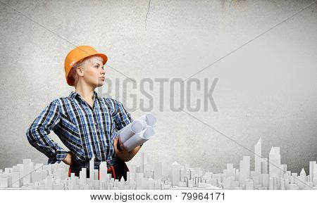 Young woman in hardhat with construction project in hands