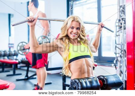 Girl training her back with exercise on machine in fitness club or gym