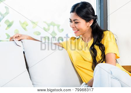 Woman customer checking price tag of sofa in Asian Indonesian furniture store showroom