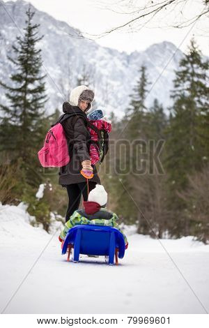 Mother Pulling A Child Through Snow On A Toboggan