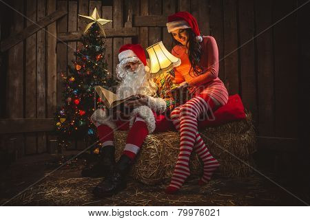 Santa Claus with his sack full of presents and helper woman