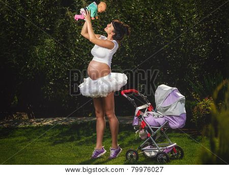 Beautiful pregnant woman having fun in garden