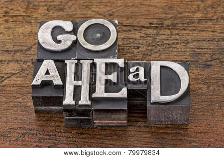 go ahead words in mixed vintage metal type printing blocks over grunge wood