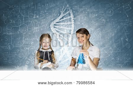 Young teacher and school girl at chemistry lesson