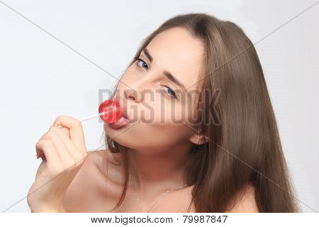 girl with beautiful hair sucks a lollipop.