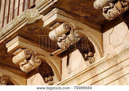 decorative stone corbels in a baroque balcony of Palazzolo Acreide, Sicily