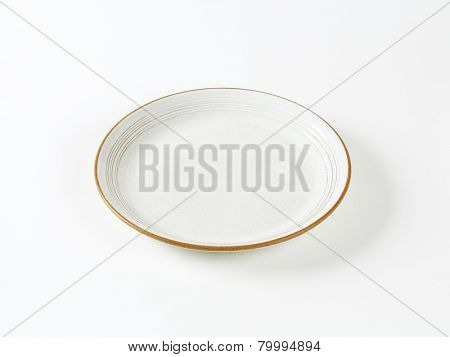 white plate with brown rim on white background
