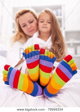 Woman and little girl wearing funny socks - cuddling after bath time