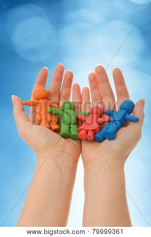 Colorful clay people in woman palm - against blurred blue background
