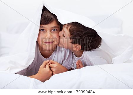 Siblings playing under the quilt - family love concept