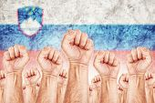picture of labourer  - Slovenia Labour movement workers union strike concept with male fists raised in the air fighting for their rights Slovenian national flag in out of focus background - JPG