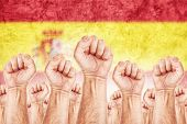 image of labourer  - Spain Labour movement workers union strike concept with male fists raised in the air fighting for their rights Spanish national flag in out of focus background - JPG