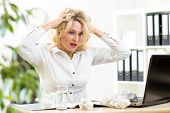 pic of frustrated  - Funny business woman frustrated and stressed holding by head looking at paper heap - JPG
