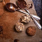 picture of truffle  - Assorted dark chocolate truffles with cocoa powder biscuit and chopped hazelnuts over baking paper selective focus - JPG