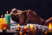 picture of seductress  - Relaxed young sexy woman in bed by candlelight - JPG
