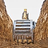 pic of excavator  - Excavator digging a deep trench on the site focus forward - JPG