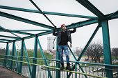 picture of anarchists  - Punk guy with beanie standing on a bridge - JPG