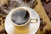 stock photo of spit-roast  - Hot morning coffee with fresh roasted coffee beans - JPG