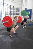 stock photo of jerks  - Two men taking squats and jerk and clean at the gym - JPG