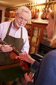 picture of leaving  - Customer Leaving Violin For Repair In Shop - JPG
