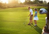 picture of pretty-boy  - Casual kids at a golf field holding golf clubs - JPG