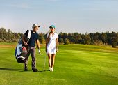 image of sportive  - Young sportive couple playing golf on a golf course walking to the next hole - JPG