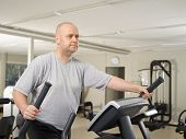 stock photo of elliptical  - Mature man takes care of his health and he use elliptical trainer in the gym - JPG