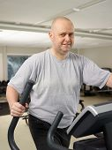 foto of elliptical  - Mature man takes care of his health and he use elliptical trainer in the gym - JPG