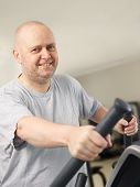 picture of elliptical  - Close up mature man takes care of his health and he use elliptical trainer in the gym - JPG