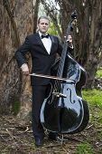 foto of double-bass  - man in tuxedo playing the double bass in park - JPG